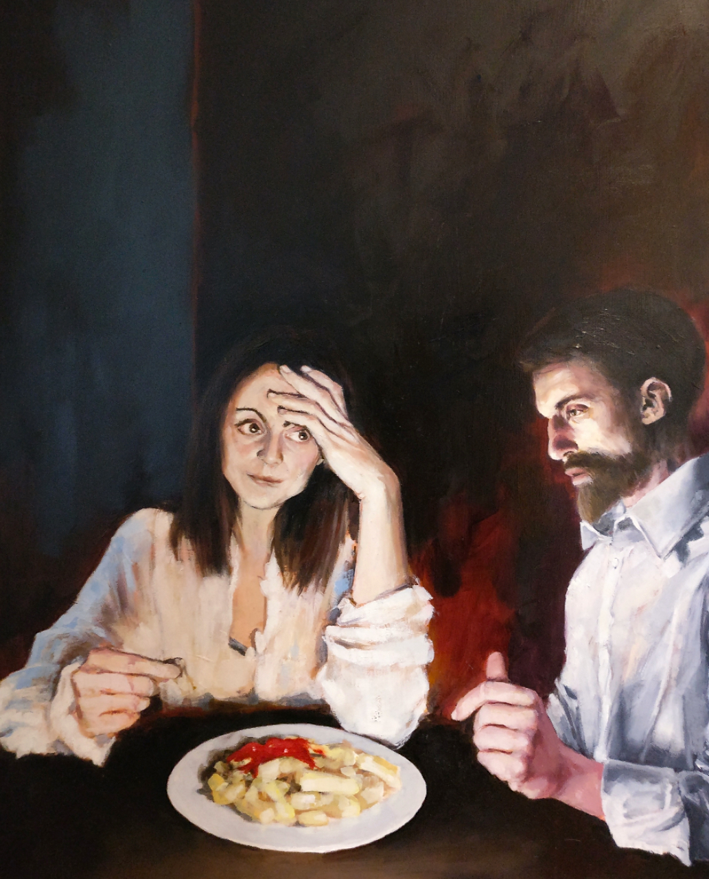 Man and Woman sitting over a plate of chips