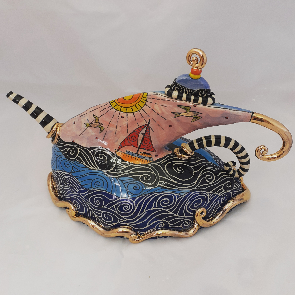 Ceramic glazed teapot in blues and navy in the shape of a boat afloat at sea