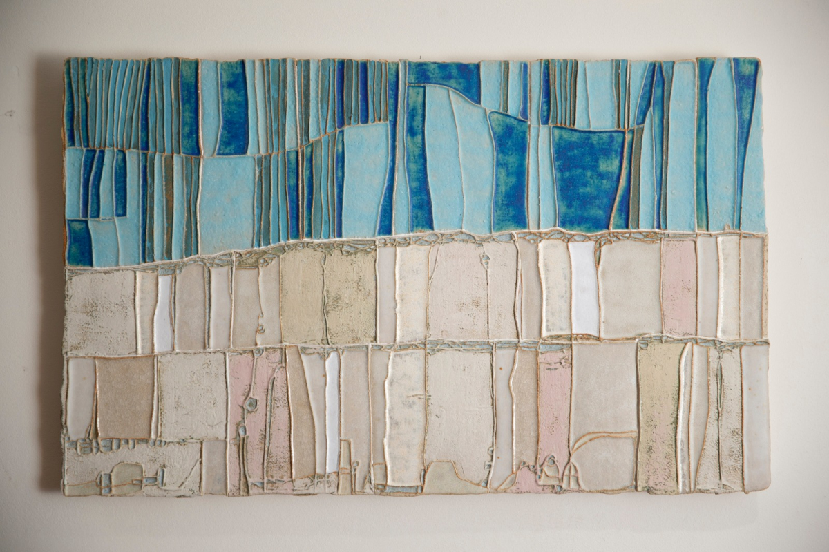 A layered wall panel with richly coloured slips and glazes