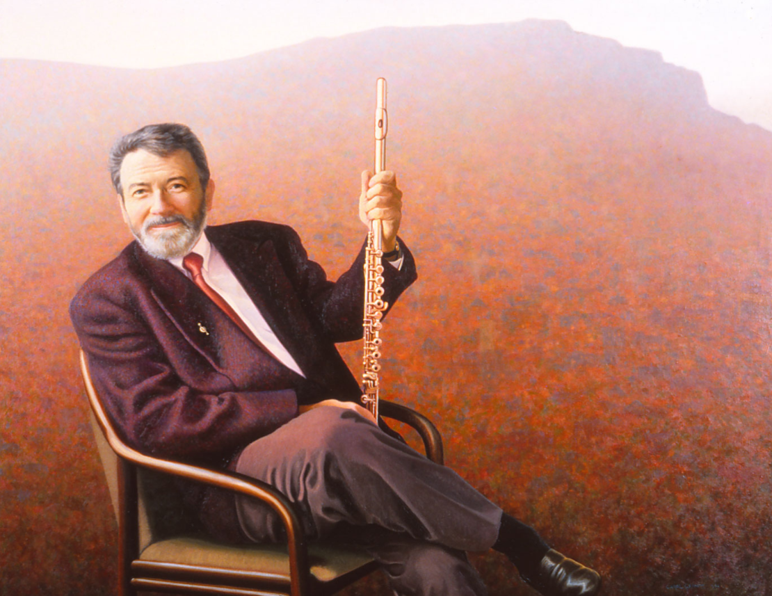 Portrait of flautist, Sir James Galway poised in a chair with his flute in his hand.
