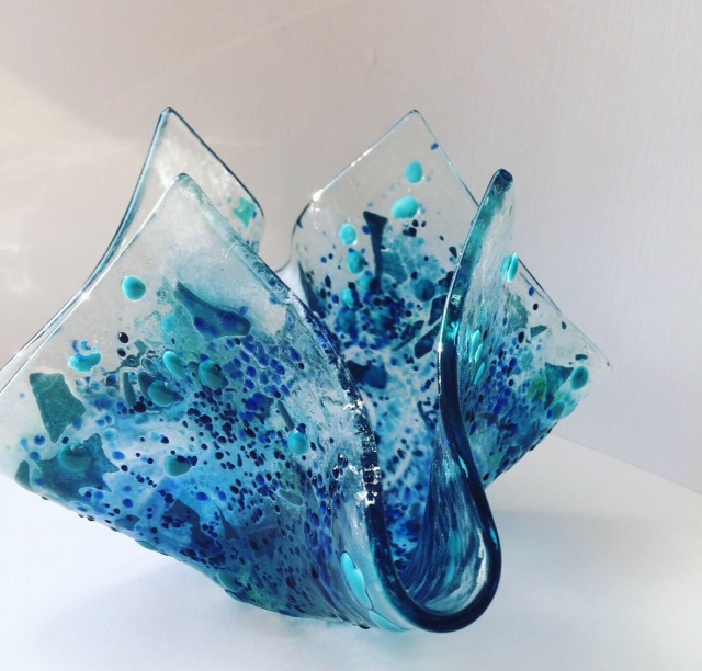 Fused glass draped and folded to replicate the effect of throwing pebbles into the sea, the moment the stone hits the water captured here in glass. Colours are various blue tones