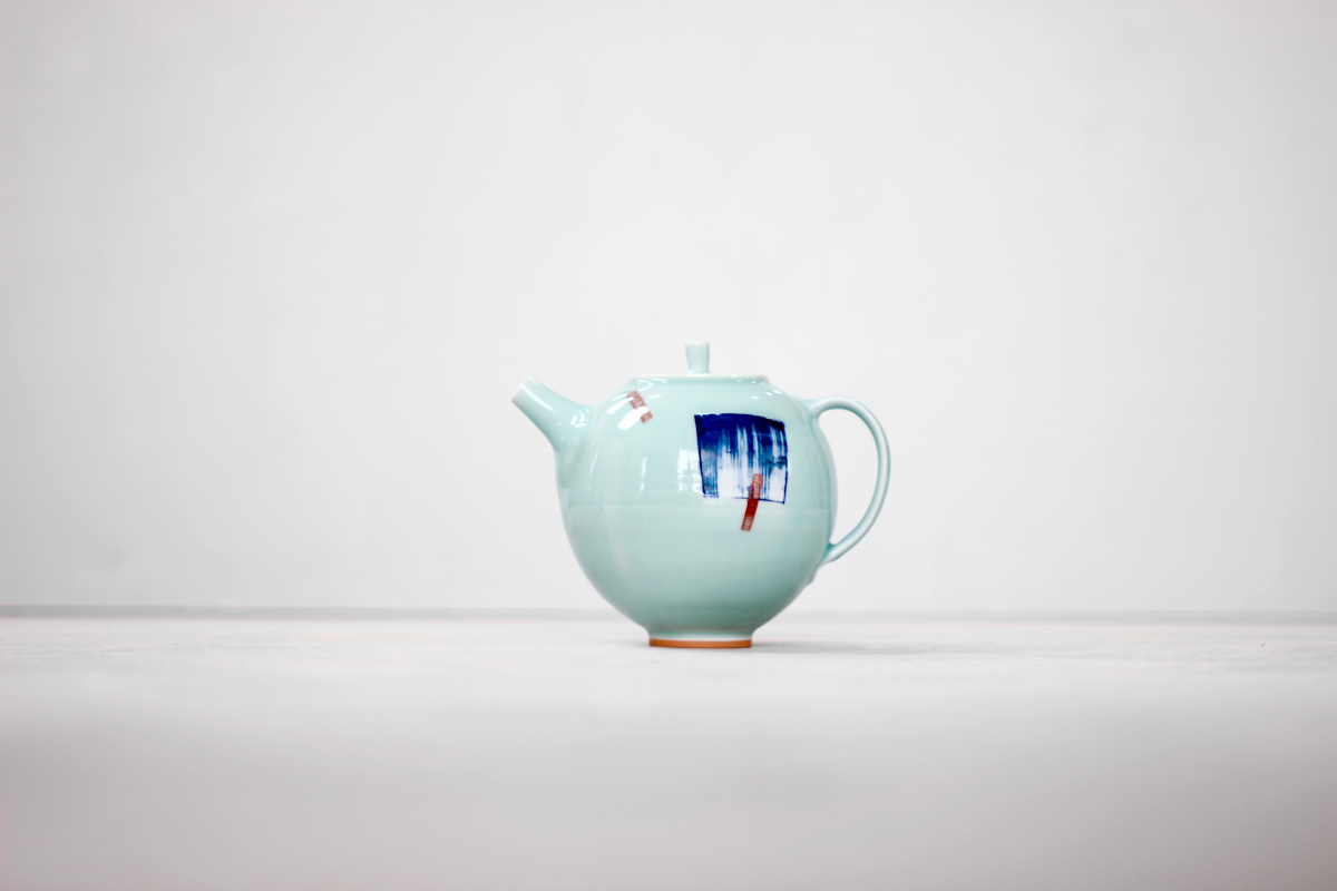 4 cup porcelain teapot with orange foot. Blue wash square pattern with red dashes, fired with a celadon (greeny blue) glaze.